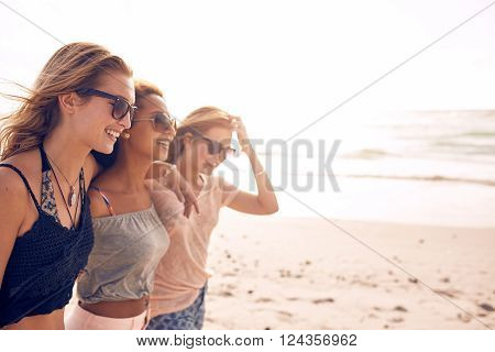 Group of happy young women walking on a beach. Three female friends strolling along the sea shore on a summer day enjoying vacation.