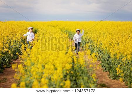 Two Adorable Children, Brothers, Running In An Oilseed Rape Field