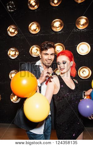 Drunk friends  clubbing dancing celebrate concept on dance club background. Woman with  colorful balloon and happy man dance on lights background. Concept of night lifestyle.
