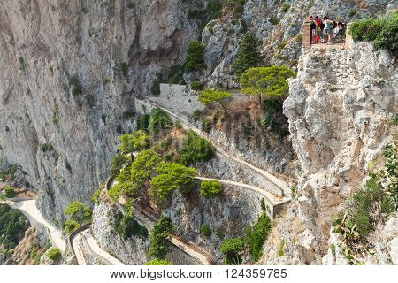 Capri, Italy - August 14, 2015: Tourists looks down on winding mountain road from high viewpoint of Capri island