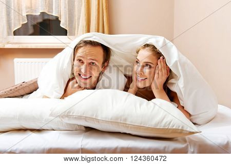 Young couple lying on bed under quilt