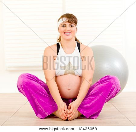 Smiling beautiful pregnant woman doing stretching exercises