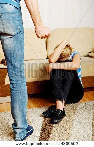 Woman trying to hide herself, man want to hit her with fist