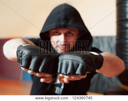 Aggressive mid adult street fighter in black hood ready to fight. Street fighter in training gloves shows his big fists. Man healthy sport lifestyle concept.