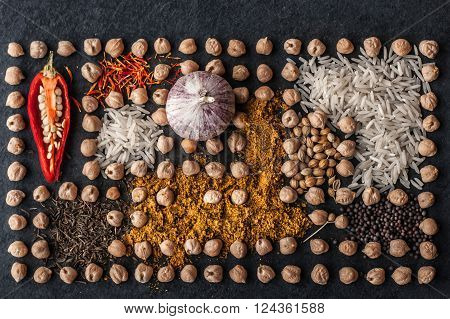 Composition of chick-pea vegetables and spice on the dark stone background