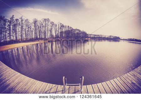 Old film vintage toned fisheye lens image of a wooden pier on lake in spring