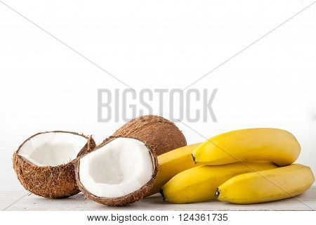 Coconuts and bananas on the white background horizontal
