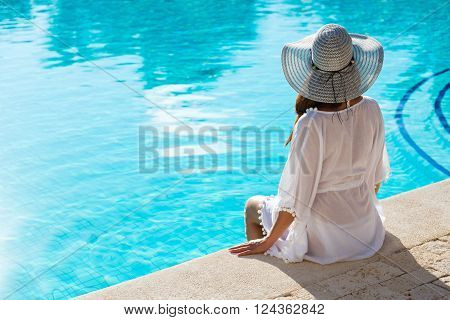 Fashionable Woman Relaxing At Poolside On Summer Vacation