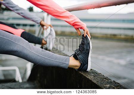 Female City Runners Stretching Legs