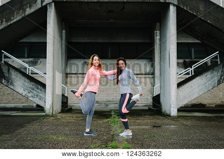 Young Women Stretching Legs Before Running