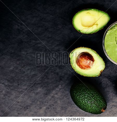 Halved and whole ripe avocados over black background. Top view.