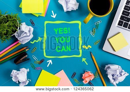 Yes You Can. Office table with notepad, computer and coffee cup on blue background. Business creative consept top view