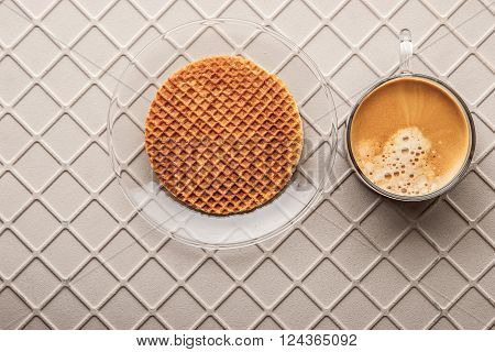 Cup of coffee with wafer on the relief background top view