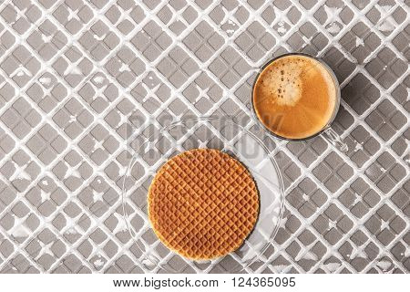 Cup of coffee with wafer on the relief background