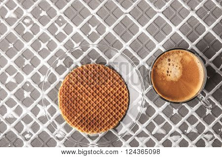 Wafer with cup of coffee on the relief background horizontal