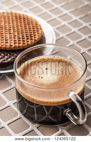 Wafers with cup of coffee on the relief background vertical
