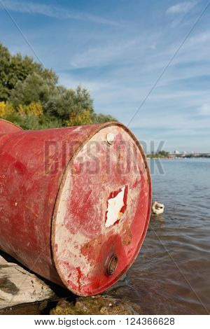 Discarded drum on the river bank, selective focus