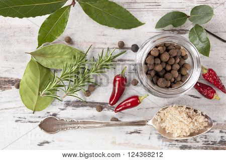 Bay leaves traditional spice and condiment on white wooden background. Bay leaves rosemary chillies and black pepper on white wooden table top view.