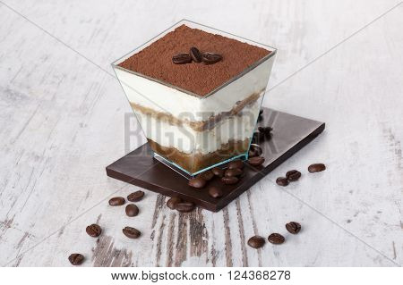 Tiramisu dessert with chocolate and coffee beans on white wooden textured table. Traditional tiramisu dessert rustic country style.