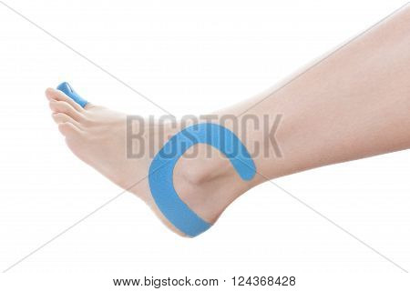 Therapeutic tape on female ankle isolated on white background. Chronic pain alternative medicine. Rehabilitation and physiotherapy.