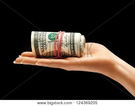 Hand holding bundle of one hundred US dollars banknotes isolated on black background. Business concept