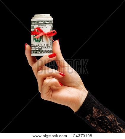 Womens Hand holding Money with red ribbon isolated on black background. Business concept