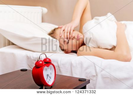 Young woman trying to sleep when alarm clock ringing