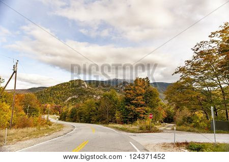 Quiet two-lane road winding through narrow valley