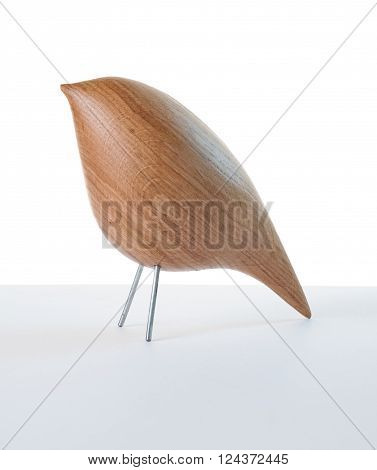 Wooden bird toy model made of natural wood standing on grey surface with white background