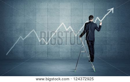 A businessman in modern stylish elegant suit standing on a small ladder and drawing pie and block charts on grey wall background with exponential progressing curves, lines,  angles, blocks, numbers