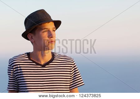 Portrait Of Serious And Pensive Young Man On Sunset Sky Background