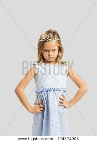 Portrait of a cute little girl with a princess crown making a sad face