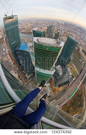 MOSCOW, RUSSIA - OCT 31, 2015: (top view, fisheye) Legs of man sitting on roof of building in International Business Center