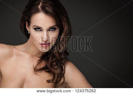 Sexy brunette woman posing on dark background