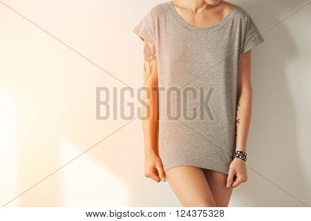 Closeup Photo Of Stylish Girl Wearing Blank T-shirt And Looking Down. Young Girl Wearing Grey Blank