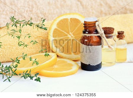Lemon esssential aroma oil. Cosmetic glass bottle, fresh fruit, thyme herb, towels.