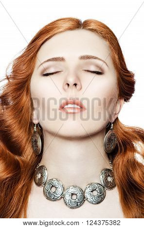 Portrait of a beautiful red-haired girl with closed eyes in the jewelry with an ethnic ornament on a white background