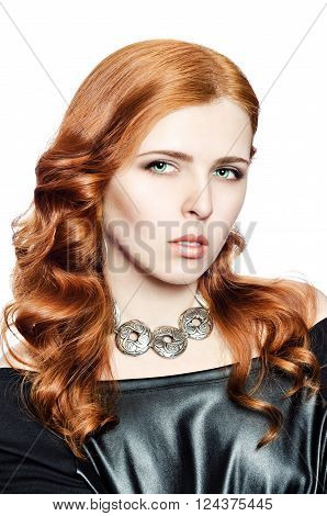 Portrait of a red-haired green-eyed girl in jewelry with an ethnic ornament on a white background