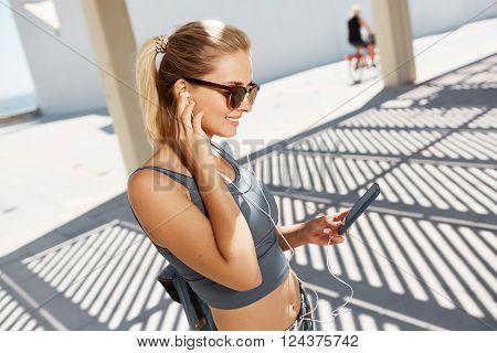 Young caucasian woman wearing sports wear looking at mobile phone. Female athlete listening music with cell phone. Girl runner enjoying the sun and listen music in earphones from smartphone.