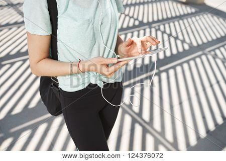 Young Asian Woman Wearing Sports Wear Looking At Mobile Phone. Female Athlete Listening Music With C