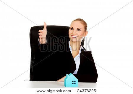 Business woman with an open hand ready for handshake and blue paper house on the desk