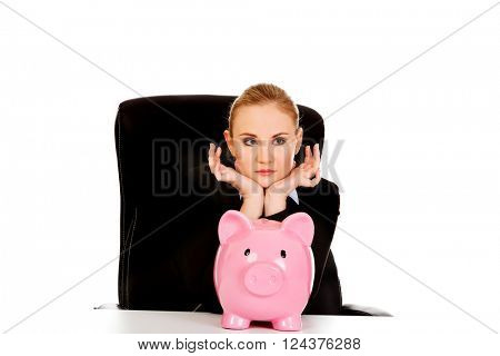 Worried business woman with a piggybank behind the desk