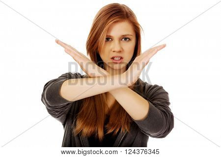 Teenage woman making stop sign with crossed hands