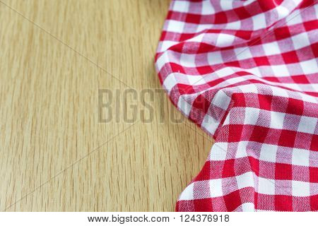 Crumpled cotton checked red and white tablecloth lies on the edge of wooden table