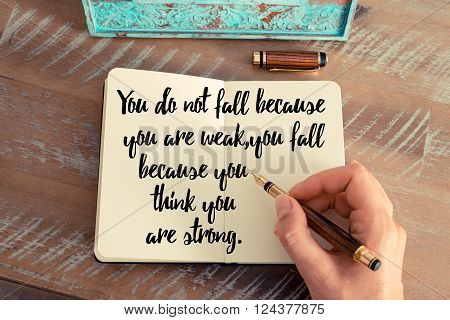 Retro effect and toned image of a woman hand writing on a notebook. Handwritten quote You do not fall because you are weak, you fall because you think you are strong. as inspirational concept image