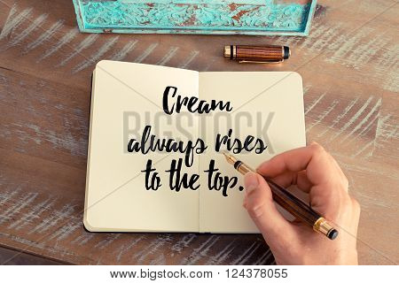 Retro effect and toned image of a woman hand writing on a notebook. Handwritten quote Cream always rises to the top as inspirational concept image