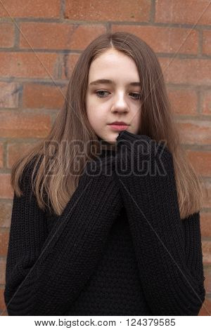 Pretty teenage girl huddling in her jumper with pensive expression