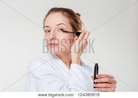 Beautiful woman applying mascara on eyelashes isolated on a white background