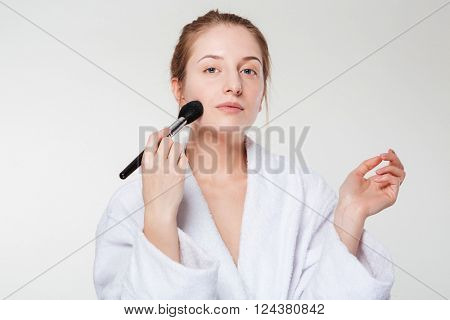 Cute woman with cosmetic brush isolated on a white background