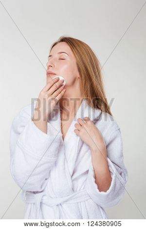 Young woman in bathrobe applying cream with cotton pad isolated on a white background